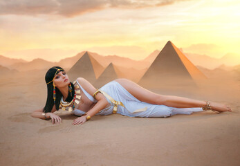 Egypt Style Rich Luxury Woman. Sexy beautiful girl goddess Queen Cleopatra lies on yellow sand desert pyramids. Art ancient pharaoh costume white dress gold accessories Black hair wig Egyptian makeup