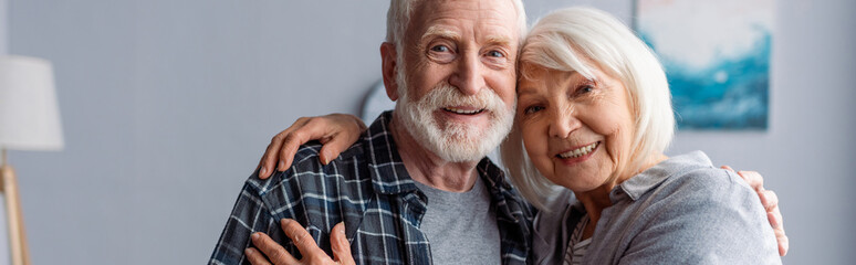 horizontal image of happy senior couple smiling and embracing while looking at camera