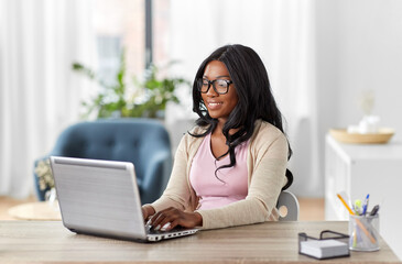 Wall Murals Equestrian remote job, business and e-learning concept - happy smiling young african american woman in glasses with laptop computer working at home office
