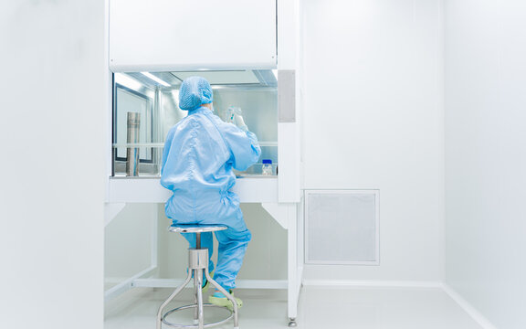 Unidentified microbiologist is testing the sample under the laminar air flow cabinet in the clean room of quality control laboratory in pharmaceutical industry.