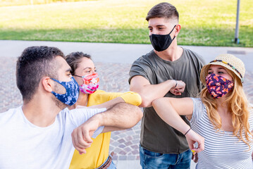 Young friends wearing the protective mask, they greet each other with new greetings, touching elbows to prevent the spread of the corona virus - Physical distance and concept of safety, new normal