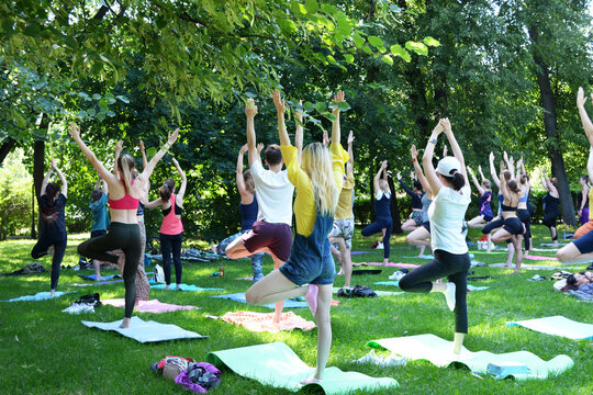 Moscow, RUSSIA - JULE 11, 2020: Group of people are engaged in yoga in the park on the Yoga Day in Moscow, Russia