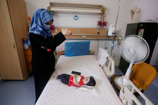 An Iraqi woman wearing a protective mask plays with her baby who suffers from cancer at the Children's Hospital for Cancer Diseases in Basra