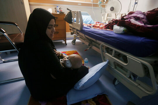 An Iraqi woman holds her child who suffers from cancer at the Children's Hospital for Cancer Diseases in Basra