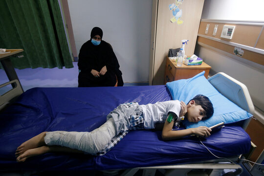 A woman rests as her son who suffers from cancer uses a mobile phone at the Children's Hospital for Cancer Diseases in Basra