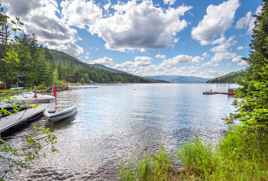 A shallow area of waterfront homes with boats and docks at Bottle Bay on Lake Pend Oreille, near the towns of Sandpoint and Sagle, Idaho, on a summer day.