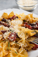 Pasta with sun dried tomatoes and parmesan in a white plate on the table. Italian food dish, vertical image