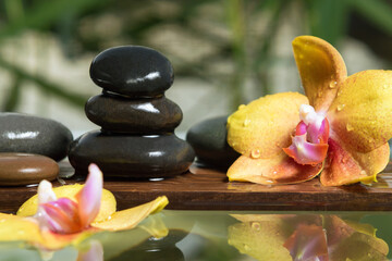 Black zen stones and yellow orchids on a wooden plank on the surface of the water. SPA, relaxation, meditation concept
