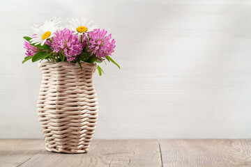 Bouquet of wildflowers, daisies and clover in a wicker vase on a wooden table. Image with copy space for postcard or design