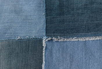 Old denim jeans texture or background made from different colored jeans peaces.