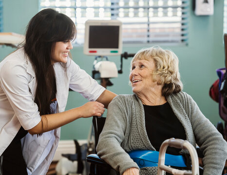 Nurse assisting senior woman in wheelchair in retirement home