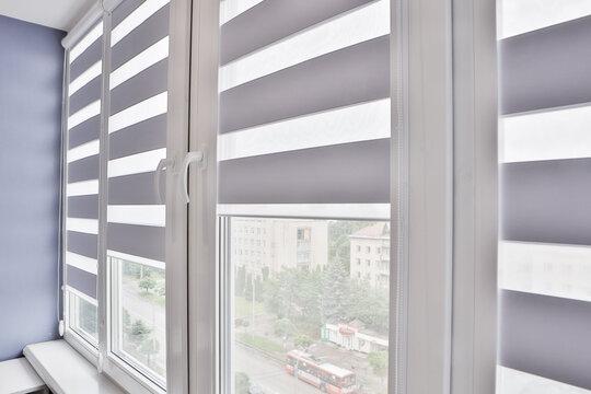 Windows with open modern horizontal blinds indoors, closeup