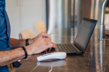 Close up of mature man's hands on keyboard of laptop with contactless thermometer next to him