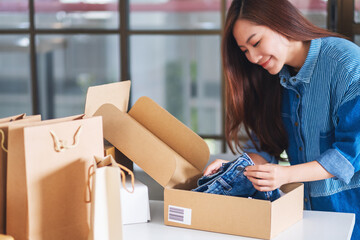A beautiful young asian woman receiving and opening a postal parcel box of clothing at home for...