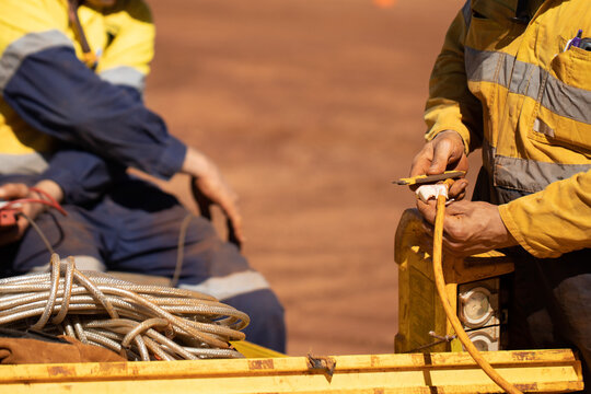 Safety workplace trained competent electrician personal standing holding yellow electricity power residual-current device RCD while inspecting safety monthly tag prior use construction site Perth