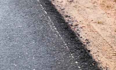 New asphalt road edge and sandy roadside