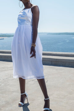 fashion african black girl in a white dress, model posing on a background of blue sky. Young african american girl model in white dress with open back posing against blue sky