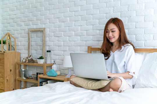 Asian beautiful woman using laptop teleconference meeting with her colleague from home during coronavirus outbreak. working from home, wfh, staycation or new normal concepts