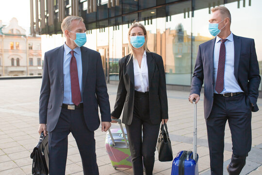 Business tourists in face masks walking outdoors with luggage, talking to each other. Front view. Business trip and epidemic concept