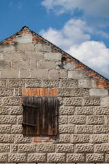 Obraz Szczytowa ściana starego wiejskiego gospodarczego budynku z drewnianymi drzwiczkami prowadzącymi na strych. - fototapety do salonu