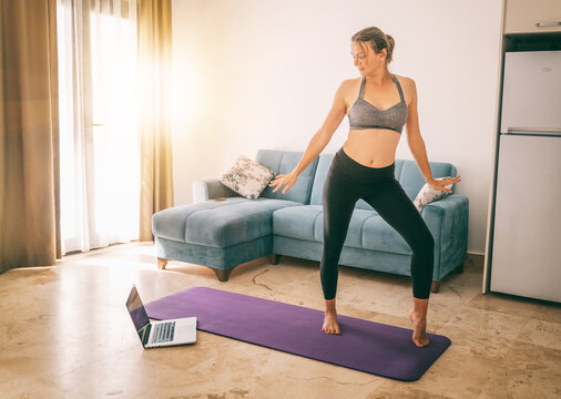 Young beautiful woman is engaged in modern dance choreography at home in front of a laptop. Sport dancing and entertainment online