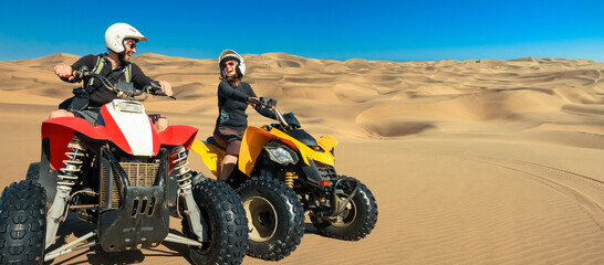 Quad ATV driving people. Happy smiling couple bikers in sand desert. Quad driving and skidmarks in sand dunes desert. Africa, Namibia, Namib, near Walvis Bay, Swakopmund. Wall mural