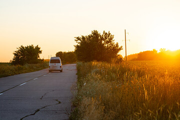 Ambulance car rides on a countryside road at sunset