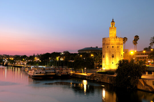 View of Golden Tower (Torre del Oro) of Seville, Andalusia, Spain by river Guadalquivir at sunset Torre del Oro of Seville by the Guadalquivir at sunset
