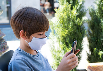 a caucasian boy wearing a mask playing mobile phone sitting in the restaurant, traveling in Europe
