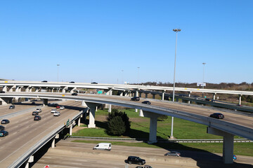 a view of a very busy interstate highway overpass exchange with multiple lanes of freeway traffic and a bright blue sky