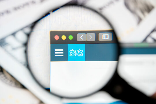 RUSSIA, ST.PETERSBURG - August 12, 2020: logo Charles Schwab Corp on the website screen through a magnifier.