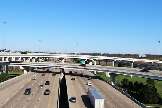 an aerial view overlooking a busy freeway interstate exchange from above with multiple lanes of freeway traffic below