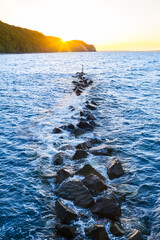 Coastal Sunset Evening Mood / Breakwater barrier of stones with warning sign near coast - sunset sky over hills at sea (copy space)