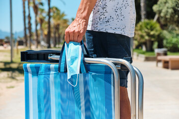 man carrying a surgical mask and a deck chair