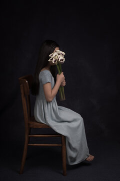 Studio portrait of an anonymous young girl in long blue dress sitting on a chair with bouquet of  white with purple arums in front of her face