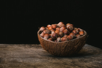 Coconut shell bowl full of hazelnuts in the shell on a wooden table on black background