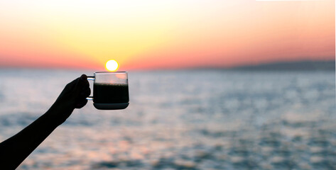 silhouette of a girl's hand with a cup of coffee or tea in the morning at sunrise on the background of the sea and sunshine. Good morning and breakfast on the beach concept. Space for text