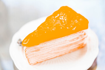 Closeup orange cake delicious on glass table background, selective focus