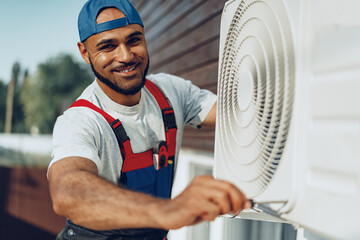Young black man repairman checking an outside air conditioner unit