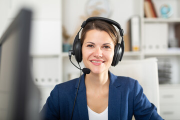 Office worker woman is working at a computer and talking by headset with client in the office
