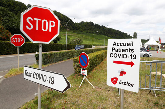 A stop traffic sign is pictured next to a sign pointing to a mobile COVID-19 test centre at the outskirts of the town of Machtum