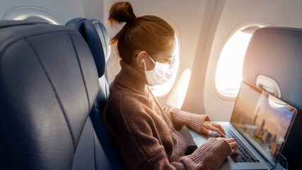 A young woman wearing face mask is traveling on airplane , New normal travel after covid-19...