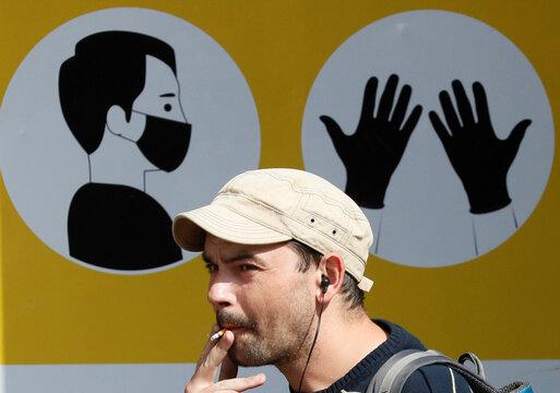 A man smokes near the entrance to a metro station in Kyiv