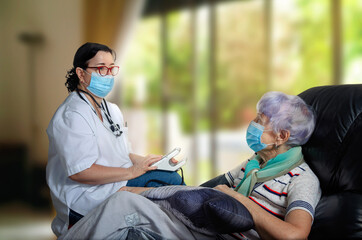 A geriatric doctor visiting an elderly patient at home to take blood pressure. However, both the patient and the geriatrician doctor are required to wear masks during a pandemic.