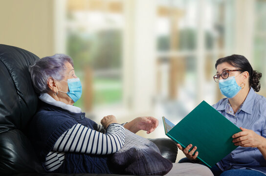 A female adult volunteer visits a single senior woman during a pandemic. She talks to her and reads books. Both wear face protective masks.