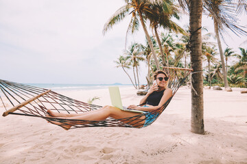 Successful female tourist in sunglasses talking on smartphone in roaming during vacations while work remotely at modern laptop computer lying on hammock on sea shore of tropical island with palm trees Wall mural