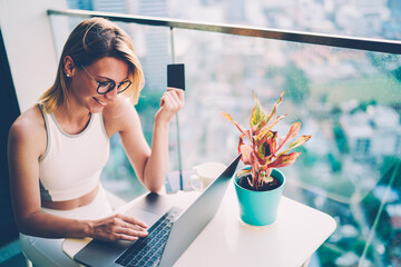 Gorgeous smiling hipster girl in eyeglasses holding credit car in hands while keyboarding information during booking. Young woman using online banking for purchase while shopping at home via laptop