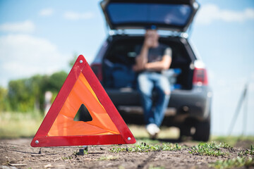 Warning triangle on the broken car background.