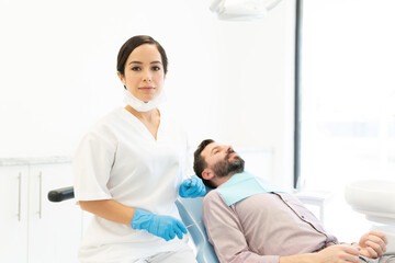 Caucasian Dentist By Patient On Chair