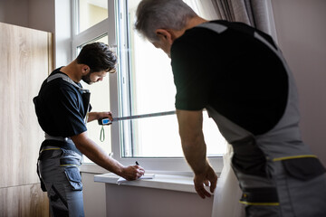 Two professional workers in uniform using tape measure while measuring window and making notes for installing blinds indoors. Construction and maintenance concept